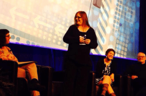 Cindy Leonard speaking on a stage with three other people